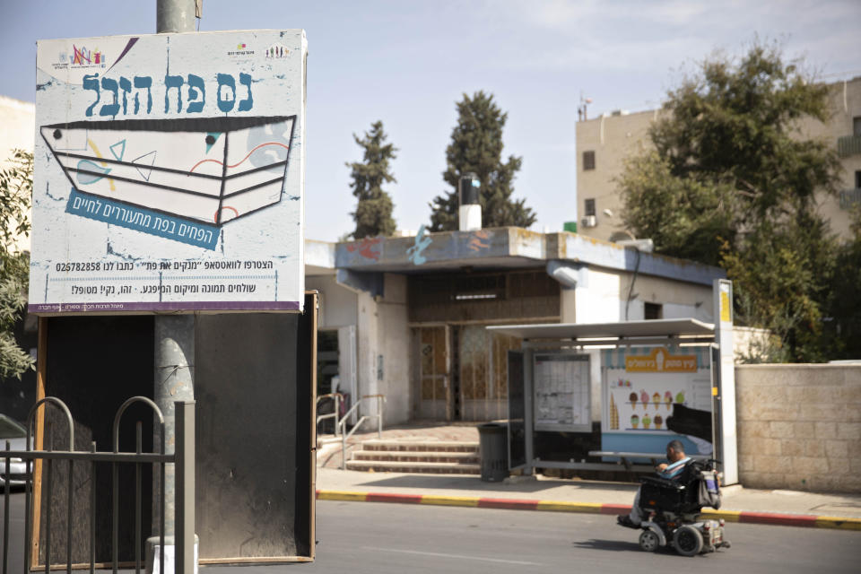 """A sign that reads """"the trash can miracle"""" hangs across the street from a trashcan installed at a bus stop that applauds to those who use it, in Jerusalem, Thursday, Oct. 14, 2021. Drop a piece of trash in, and a recording of a child's voice says, """"Thank you very much!"""" (AP Photo/Sebastian Scheiner)"""