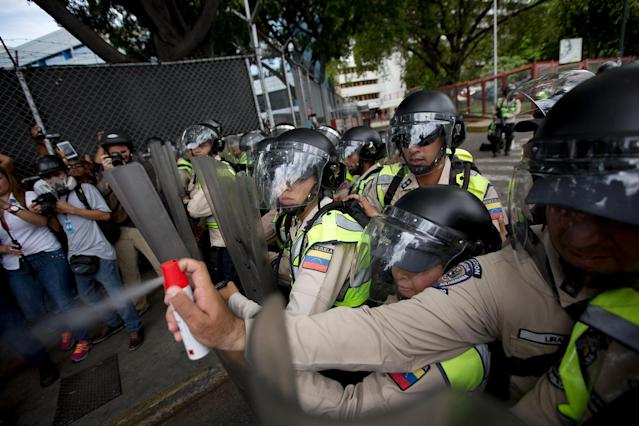<p>A police officer aims pepper spray at opposition leader Henrique Capriles during a protest in Caracas, June 7, 2016. (AP/Fernando Llano) </p>