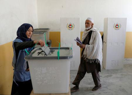 An Afghan man arrives as a woman casts her vote during parliamentary elections at a polling station in Kabul