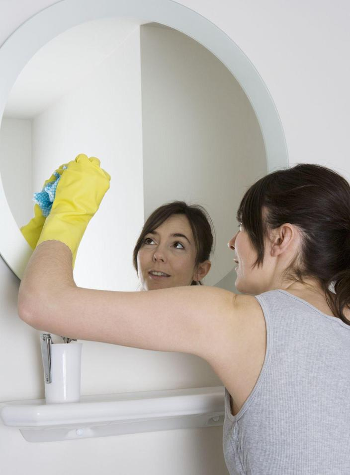 """<p>According to Molly Maid, a <a href=""""https://www.mollymaid.com/cleaning-tips/bathrooms/how-to-clean-a-mirror/"""" rel=""""nofollow noopener"""" target=""""_blank"""" data-ylk=""""slk:streak-free mirror can be achieved"""" class=""""link rapid-noclick-resp"""">streak-free mirror can be achieved</a> using half a cup of distilled water, half a cup of white vinegar, and one tablespoon of corn starch. Mix those ingredients in a spray bottle and then spritz the mirror with your cleaning solution. Then, use a microfiber cloth or crumbled-up newspaper to wipe across the mirror in a broad """"S"""" pattern, working from top to bottom. </p><p>Any particularly stubborn debris can be removed before you start cleaning with rubbing alcohol and a clean cloth. Simply dip a corner of the cloth in the alcohol to scrub the debris before you clean the rest of the mirror glass.</p>"""