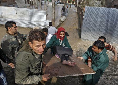 An ailing woman is carried on a wooden plank to a safer place from her partially submerged house after incessant rains in Srinagar March 30, 2015. REUTERS/Danish Ismail