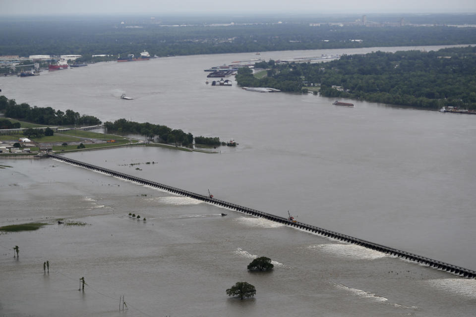 File - In this May 10, 2019 file photo, workers open bays of the Bonnet Carre Spillway, to divert rising water from the Mississippi River to Lake Pontchartrain, upriver from New Orleans, in Norco, La. The river that drains much of the flood-soaked United States is running far higher than normal this hurricane season, menacing New Orleans in multiple ways. One continuing concern is the massive volume of water that for months has been pushing against levees protecting a city that's mostly below sea level. (AP Photo/Gerald Herbert, File)