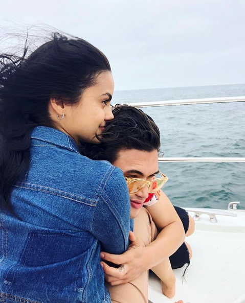 A photo of Riverdale couple Camila Mendes and Charles Melton sharing a hug on a boat