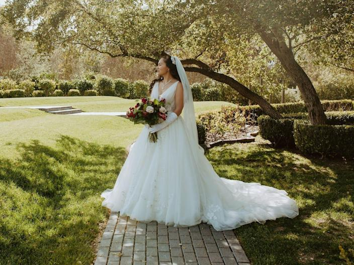 A bride stands on a pathway in front of a field holding a bouquet.