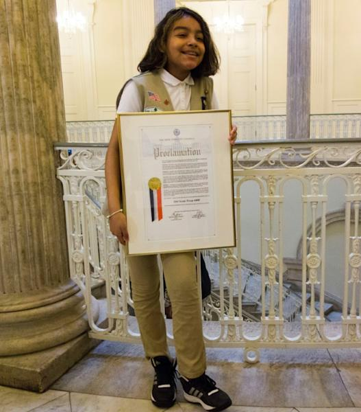 Karina, a member of Girl Scout Troop 6000, poses with the troop's proclamation