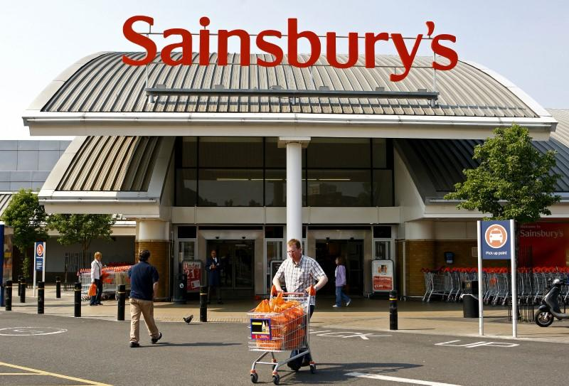 Customers walk in front of a Sainsbury's store in south London
