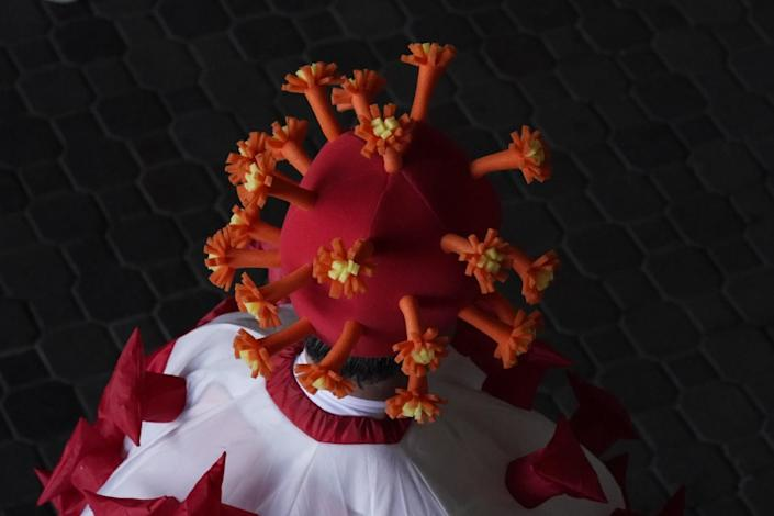 A man wears a hat that looks like the coronavirus with a red base and orange and yellow flower-like extensions.