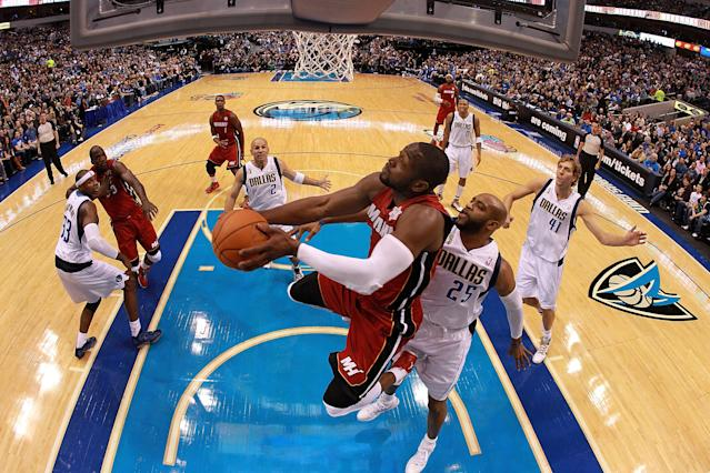 DALLAS, TX - DECEMBER 25: Dwyane Wade #3 of the Miami Heat takes a shot against Vince Carter #25 of the Dallas Mavericks during the NBA season opening game at American Airlines Center on December 25, 2011 in Dallas, Texas. NOTE TO USER: User expressly acknowledges and agrees that, by downloading and/or using this Photograph, user is consenting to the terms and conditions of the Getty Images License Agreement. (Photo by Ronald Martinez/Getty Images)