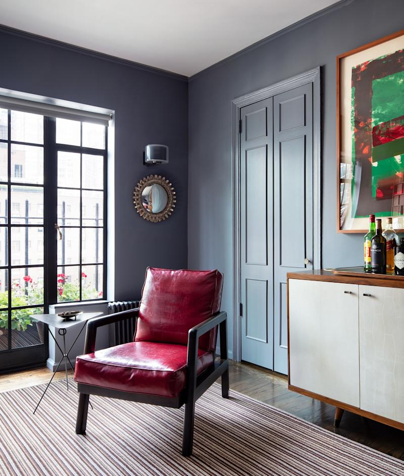 The bedroom walls are painted in Benjamin Moore's Rock Gray. The vintage leather-and-maple armchair, the blackened-steel side table, and the Line Vautrin mirror are all from Maison Gerard. A piece by Howard Hodgkin hangs above a custom-made Brazilian-walnut-and-parchment sideboard.