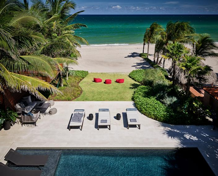 """<div class=""""caption""""> Golden Beach, the exclusive enclave where Joyner's home sits, is famed for its seclusion. Homeowners have the rarity of private coastline, of which Joyner takes advantage with both a pool terrace and a manicured grass area that leads right to the sand. <a href=""""https://www.enea.ch/?lang=en"""" rel=""""nofollow noopener"""" target=""""_blank"""" data-ylk=""""slk:Enea Landscape Architecture"""" class=""""link rapid-noclick-resp"""">Enea Landscape Architecture</a> designed all the outdoor space. </div>"""