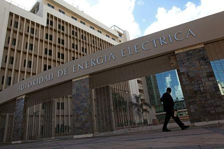 A man walks past the headquarters of the Puerto Rico Electric Power Authority (PREPA) in San Juan