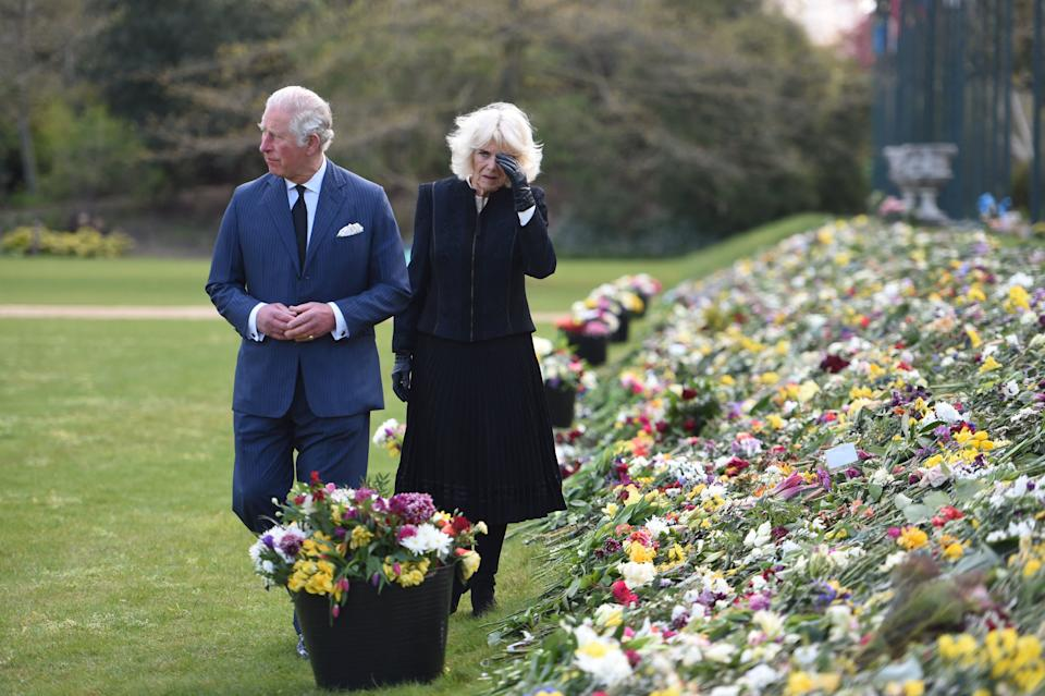 Britain's Prince Charles, Prince of Wales (L) and Britain's Camilla, Duchess of Cornwall visit the gardens of Marlborough House in London on April 15, 2021, to view the flowers and messages of condolence left by members of the public outside Buckingham Palace, following the April 9 death of Britain's Prince Philip, Duke of Edinburgh. - The Duke of Edinburgh, who died last Friday, will be buried on April 17 at Windsor Castle, west of London, with just 30 mourners, most of them close family. (Photo by Jeremy SELWYN / POOL / AFP) (Photo by JEREMY SELWYN/POOL/AFP via Getty Images)