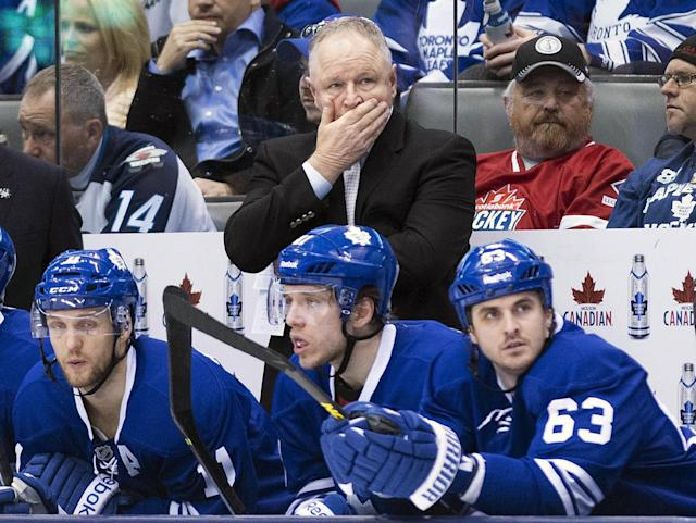 Toronto Maple Leafs head coach Randy Carlyle, top center, looks on in the final minutes of an NHL hockey game against the Winnipeg Jets during third-period NHL hockey game action in Toronto, Saturday, April 5, 2014. The Jets won 4-2. (AP Photo/The Canadian Press, Nathan Denette)