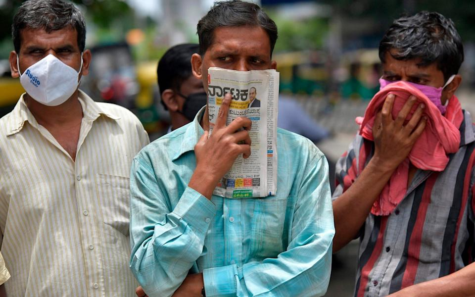 A man holds a newspaper to cover his face in the absence of his facemask in Bangalore - AFP