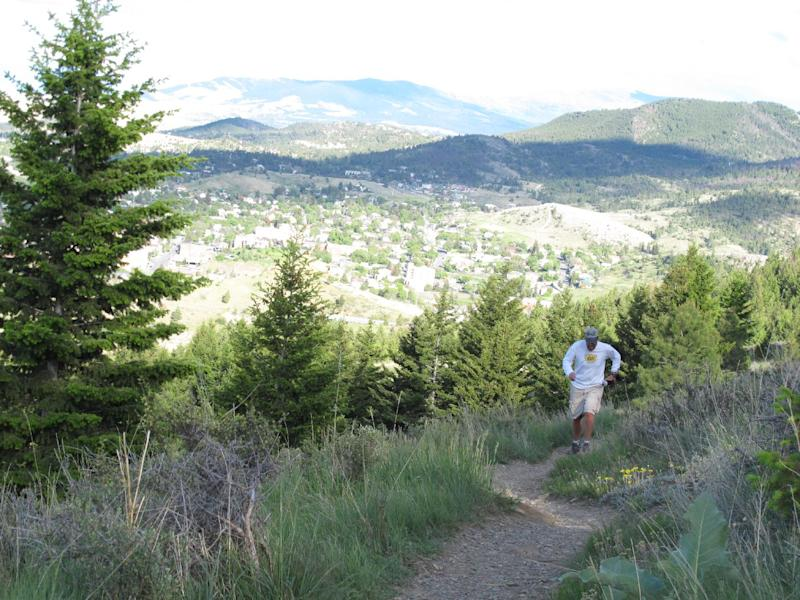 This June 9, 2012 photo shows a jogger runs along a trail on Mount Helena on June 9, 2012, in Helena, Mont. The Helena Ridge Trail, which ends at the 5,400-foot summit of Mount Helena, is one of the Montana capital's top attractions. (AP Photo/Matt Volz)