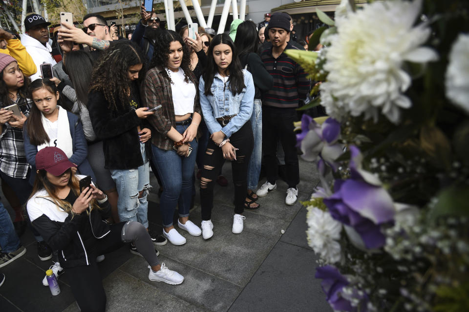 People gather at a makeshift memorial honoring former NBA player Kobe Bryant outside of the Staples Center prior to the start of the 62nd annual Grammy Awards at the Staples Center on Sunday, Jan. 26, 2020, in Los Angeles. Bryant died Sunday in a helicopter crash near Calabasas, Calif. He was 41. (AP Photo/Chris Pizzello)