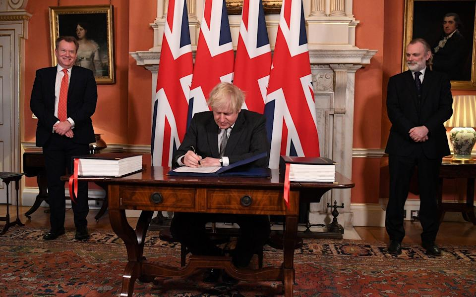 Lord Frost, pictured far left, watches on as Boris Johnson signs the Brexit trade deal - Getty
