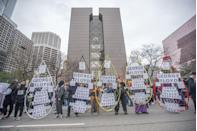 <p>Protesters hold up artwork for the protest in front of the Hennepin County Government Center on the day of closing arguments.</p>