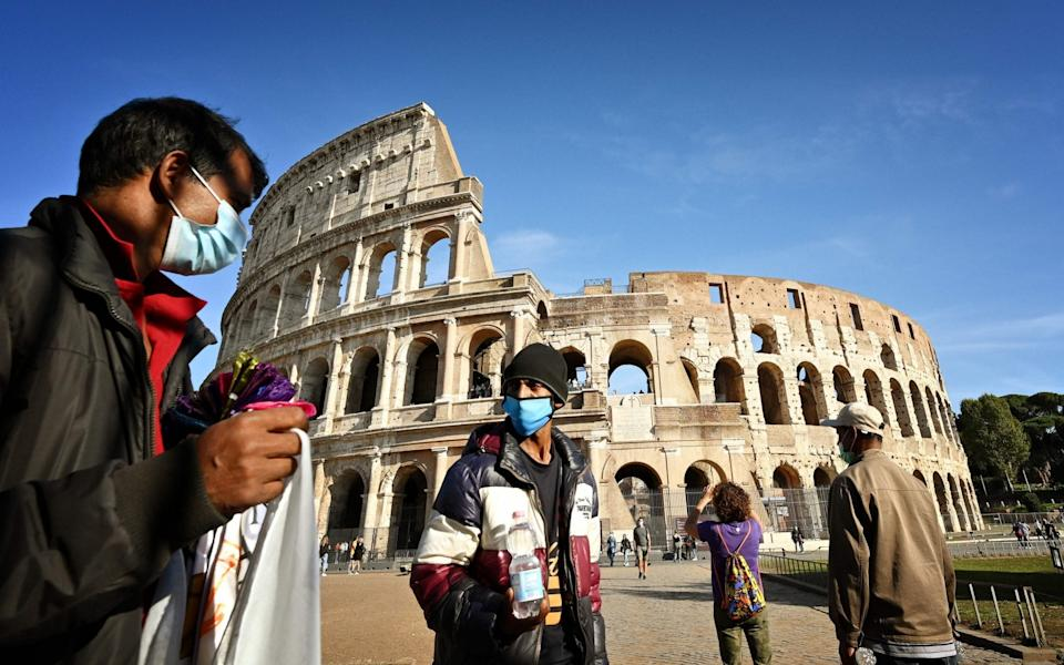 Street vendor wear face masks as they ply their trade in front of The Colosseum in Rome