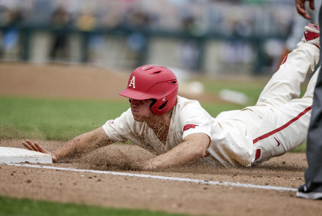 Arkansas' Jared Gates slides back to first base after overshooting it on a single in the fourth inning of an NCAA College World Series baseball game against Texas in Omaha, Neb., Sunday, June 17, 2018. (AP Photo/Nati Harnik)