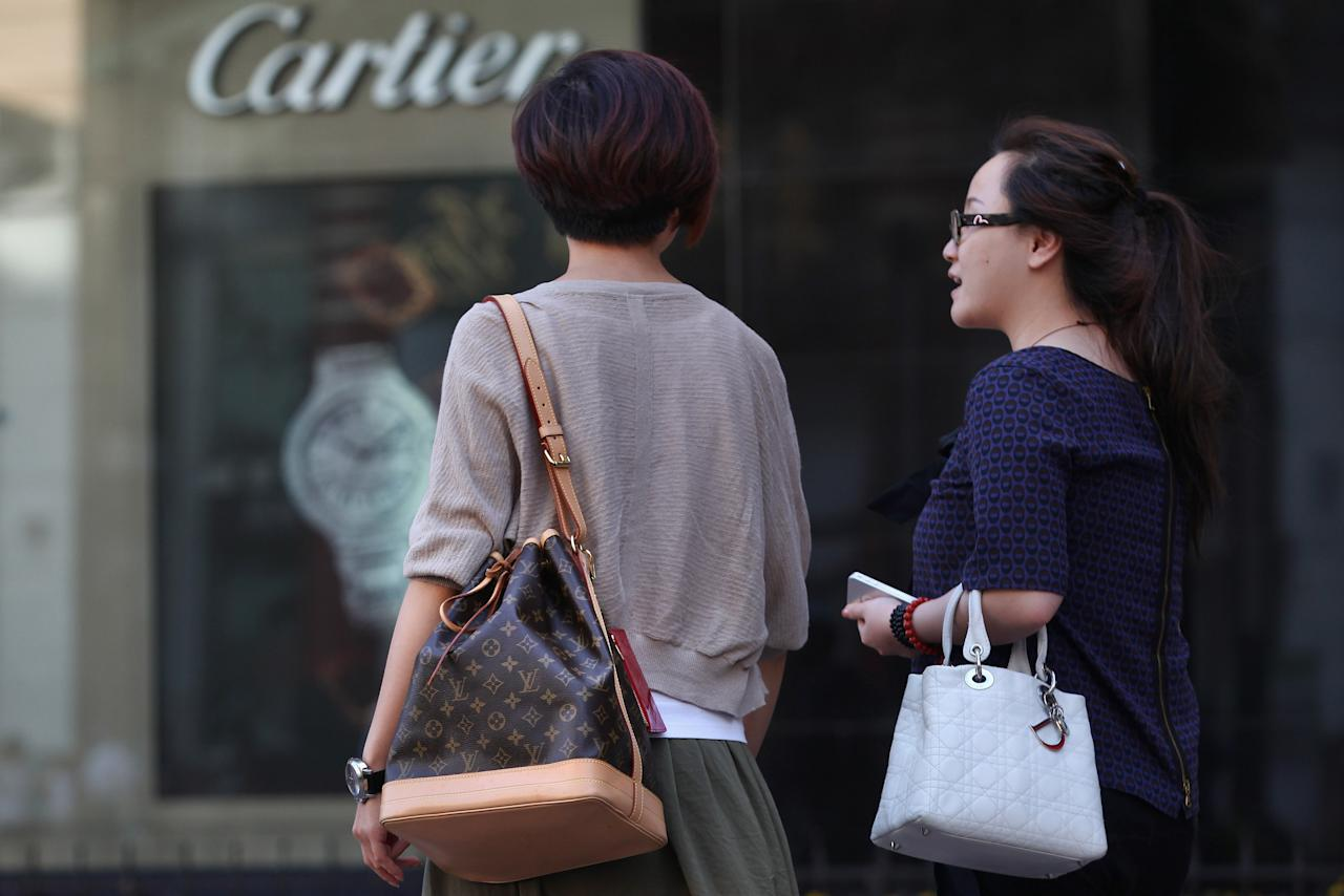 BEIJING, CHINA - JUNE 11:  Chinese women walk past the Cartier store on June 11, 2012 in Beijing, China. According to the World Luxury Association 2011 annual official report , China is expected to replace Japan as the world's top consumer of luxury goods by 2012 with an expected luxury goods sales value of 14.6 billion U.S. dollars due to China's growing demand and declining consumption in Japan.  (Photo by Feng Li/Getty Images)