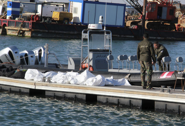 Tunisian coast guards stand next to the clovered dead bodies of migrants in the port of Sfax, central Tunisia, Thursday, Dec. 24, 2020. About 20 African migrants were found dead Thursday after their smuggling boat sank in the Mediterranean Sea while trying to reach Europe, Tunisian authorities said. Coast guard boats and local fishermen found and retrieved the bodies in the waters off the coastal city of Sfax in central Tunisia. (AP Photo/Houssem Zouari)