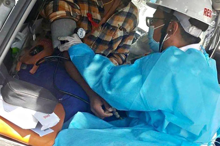 """In this March 5, 2021 photo obtained by The Associated Press, Dr. Nay Lin Tun tends to a patient wounded in a protest in Yangon, Myanmar. """"In other country's protests, the medics are safe. They are exempt. Here, there are no exemptions,"""" says the general practitioner who has been on the run since February, and now provides care covertly. (AP Photo)"""