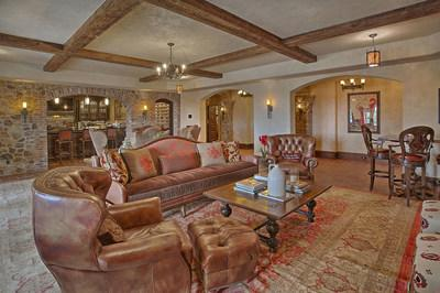 Cozy and inviting, the lower-level lounge (pictured here) offers a temperature-controlled wine cellar and wet bar, and is just down the hall from the home theater, digital golf simulation room and an additional kitchen. NewJerseyLuxuryAuction.com.