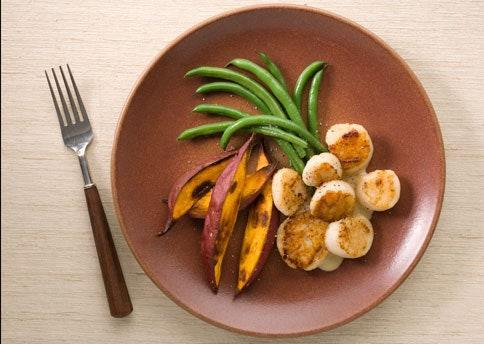 """The new meat-and-three is scallops with sweets n' beans. <a href=""""https://www.bonappetit.com/recipe/pan-roasted-scallops-with-roasted-sweet-potatoes?mbid=synd_yahoo_rss"""" rel=""""nofollow noopener"""" target=""""_blank"""" data-ylk=""""slk:See recipe."""" class=""""link rapid-noclick-resp"""">See recipe.</a>"""