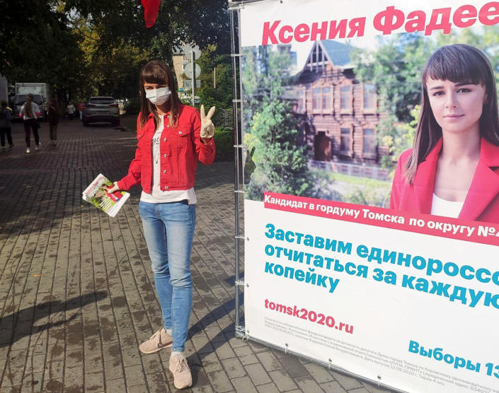 In this August 2020 photo provided by Alexei Navalny's team, Ksenia Fadeyeva, who is running for the city council in Tomsk, Russia, poses for a photo next to her election poster. Fadeyeva has secured a seat in the city council, according to preliminary results of the regional election that took place on Sunday, Sept. 13, 2020. (Andrei Fateyev/Alexei Navalny's team via AP)