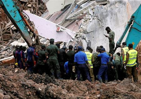Members of the military work during a rescue mission after a garbage dump collapsed and buried dozens of houses in Colombo, Sri Lanka