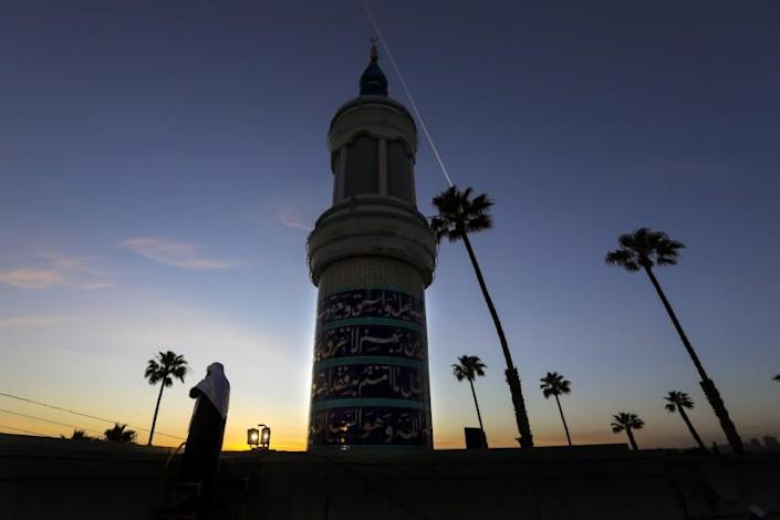"""Mahmood Nadvi, standing on the rooftop, delivers the adhan, the Islamic call to prayer, at King Fahad Mosque in Culver City. Amid the pandemic lockdown, many mosques in Southern California got permission from local authorities to broadcast the adhan during Ramadan, the holiest month in the Islamic calendar. <span class=""""copyright"""">(Irfan Khan / Los Angeles Times)</span>"""
