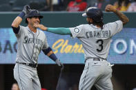 Seattle Mariners' Dylan Moore (25) celebrates his two-run home run with J.P. Crawford (3) during the second inning against the Texas Rangers in a baseball game Friday, May 7, 2021, in Arlington, Texas. (AP Photo/Richard W. Rodriguez)