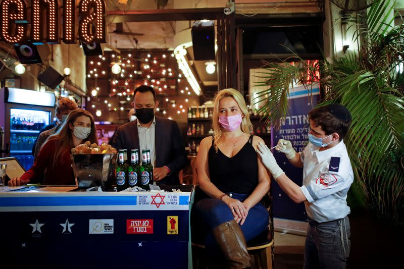 FILE PHOTO: A woman receives a vaccination against the coronavirus disease (COVID-19) as part of a Tel Aviv municipality initiative offering a free drink at a bar to residents getting the shot, in Tel Aviv