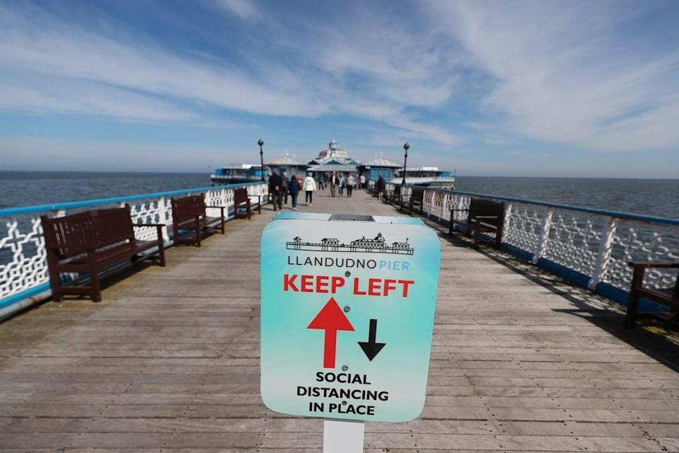 A social distancing sign on the pier in Llandudno (Peter Byrne/PA) (PA Wire)