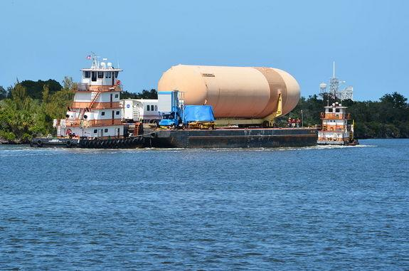 On its way to the Intercoastal Waterway, the barge carrying the external tank and other shuttle artifacts for the Wings of Dreams Aviation Museum is seen with Kennedy Space Center's Launch Pad 39A in the background, April 24, 2013.