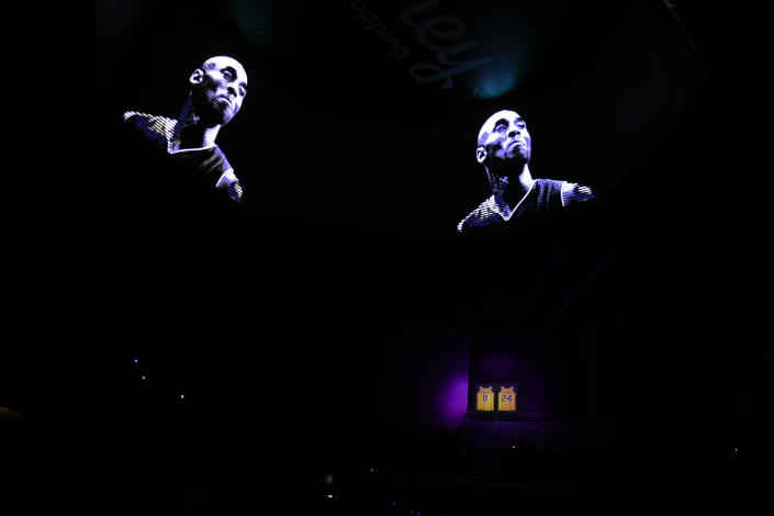 FILE - In this Jan. 30, 2020, file photo, a video is played in remembrance of late Los Angeles Lakers player Kobe Bryant while his retired jerseys hang in the rafters prior an NBA basketball game between the Los Angeles Clippers and the Sacramento Kings in Los Angeles. (AP Photo/Kelvin Kuo, File)