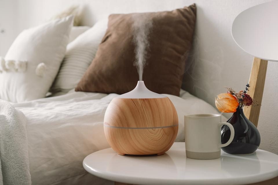Aromatherapy Concept. Aroma oil diffuser on chair against in the bedroom. Air freshener. Ultrasonic aroma diffuser for home