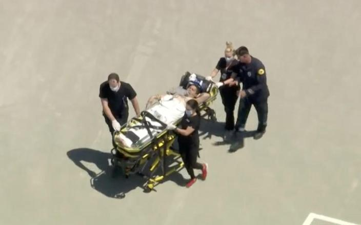 Four emergency workers push a gurney carrying a patient.