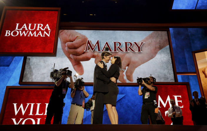 Bradley Thompson, production manager for the Republican National Convention, left, proposes to his girlfriend Laura Bowman, a production coordinator, on the stage of the convention hall, Wednesday, Aug. 29, 2012, in Tampa, Fla. (AP Photo/David Goldman)