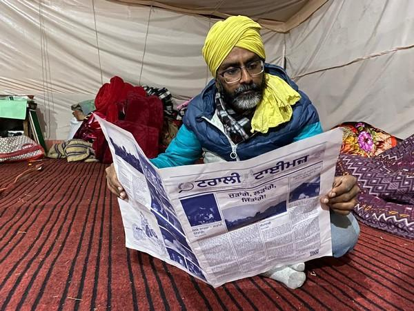 Writer Surmeet Maavi at Delhi's Singhu border reading a copy of the first edition of bi-weekly newsletter Trolley Times. (Photo/ ANI)
