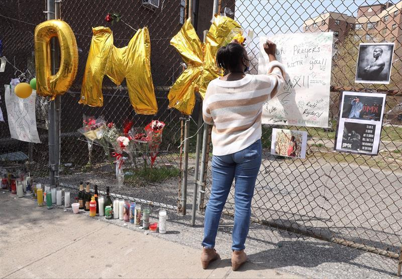 A mourner signs a poster at a memorial for DMX outside White Plains Hospital April 9, 2021.