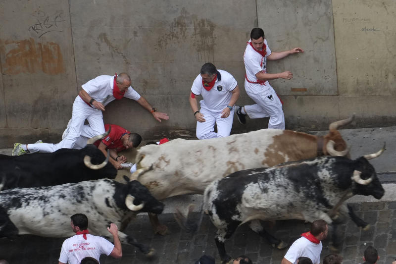 Participants run in front of Torrestrella's bulls during the first bull-run of the San Fermin Festival in Pamplona, northern Spain, on July 7, 2014 (AFP Photo/Pedro Armestre)