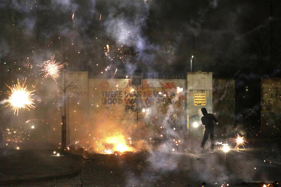 Fireworks explode as Nationalist and Loyalist rioters clash with one another at the peace wall on Lanark Way in West Belfast, Northern Ireland, Wednesday, April 7, 2021. The police had to close roads into the near by Protestant area as crowds from each divide attacked each other. (AP Photo/Peter Morrison)
