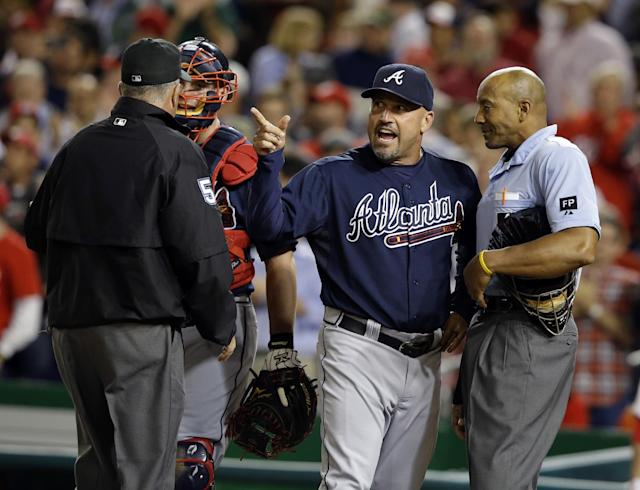 Atlanta Braves manager Fredi Gonzalez, second from right argues with home plate umpire CB Bucknor, right with umpire Dale Scott, left, and catcher Brian McCann during the fifth inning of a baseball game against the Washington Nationals at Nationals Park, Wednesday, Sept. 18, 2013, in Washington. Bucknor called a pitch a ball with the bases loaded and a full count. (AP Photo/Alex Brandon)