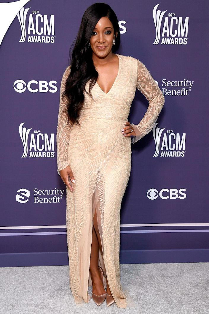 <p>goes sexy and sleek in a Naeem Khan V-neck long-sleeve embroidered gown, paired with Stuart Weitzman heels. </p>