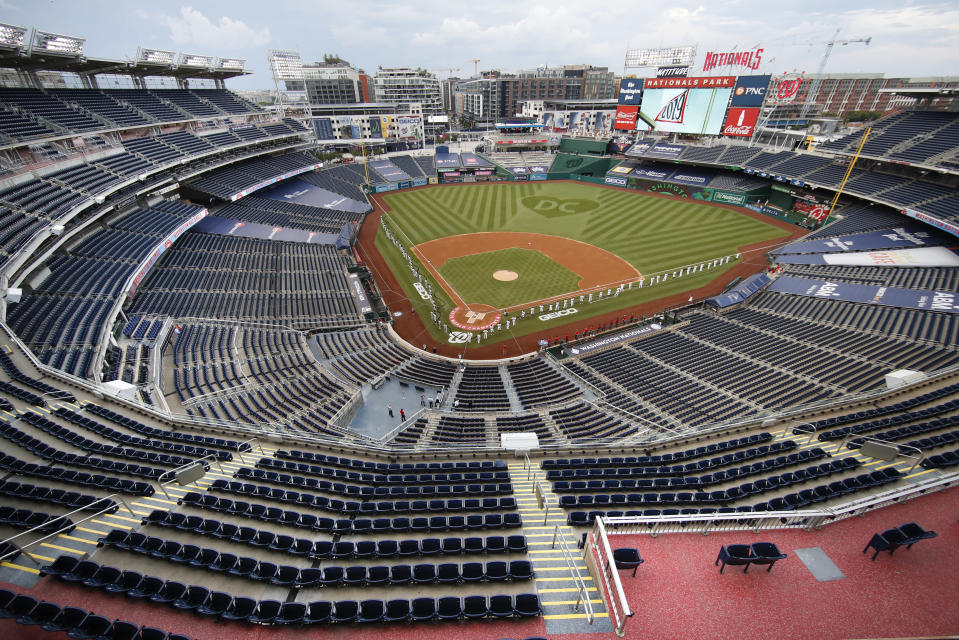 The New York Yankees and the Washington Nationals stand on the field before their opening day baseball game with no fans in the seats at Nationals Park, Thursday, July 23, 2020, in Washington. (AP Photo/Alex Brandon)