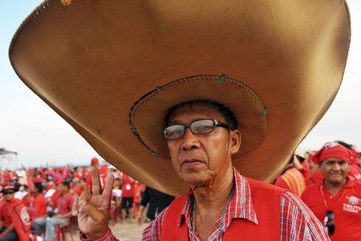 "A ""Red Shirt"" supporter of Thailand's fugitive former premier Thaksin Shinawatra at a rally in Siem Reap province, Cambodia, on Saturday. Thaksin told the rally Thailand can begin to heal its deep political rifts"