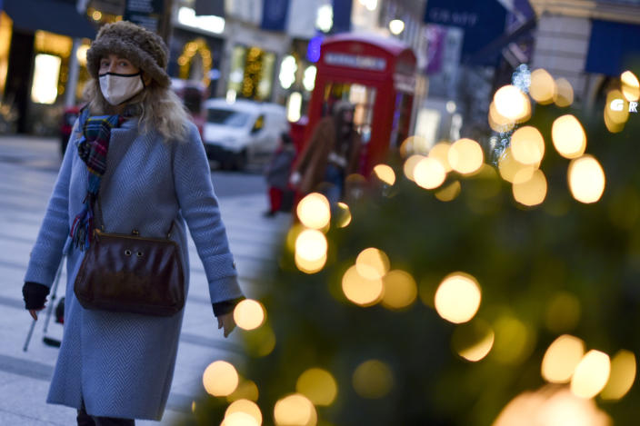 A woman wears a face mask as she walks past a Christmas tree in New Bond Street, in London, Tuesday, Dec. 22, 2020. Britain's Prime Minister Boris Johnson cancelled Christmas for almost 18 million people across London and eastern and south-east England, following warnings from scientists of the rapid spread of the new variant of coronavirus.(AP Photo/Alberto Pezzali)