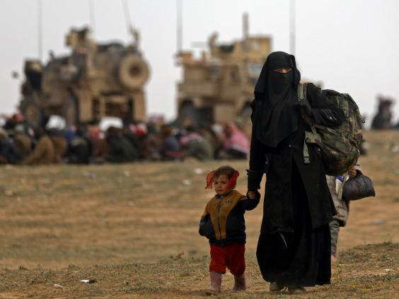 Civilians flee the last Isis enclave in Baghouz as Syrian Democratic Forces battle to liberate the village (AFP/Getty)